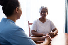 Side view of nurse interacting with senior woman at table Royalty Free Stock Images