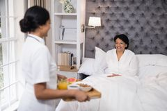 Side view of nurse serving breakfast to patient resting on bed at home royalty free stock photos