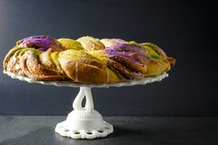 Free Side View Of A Festive Mardi Gras King Cake With Green, Gold, And Purple Frosting On A White Cake Stand With A Gray Background Stock Image - 173386031