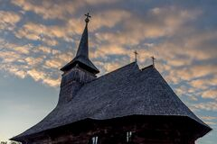 Free Side View Of An Old Wooden Church With Bell Tower On A Cloudy Blue Sunset Sky In Maramures Stock Photos - 175417293