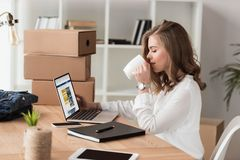 Side View Of Businesswoman Drinking Coffee While Working On Laptop Stock Photography