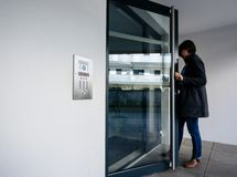Free Side View Of Woman Entering Apartment Building Intercom Access Stock Photos - 155849393