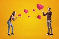 Free Side View Of Young Couple On Amber Background Playing With Cute Valentine Hearts That Float In Air, Man Trying To Catch Stock Photo - 181943770