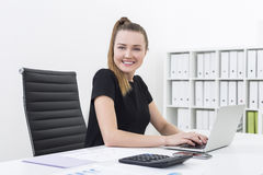 Side view of an office clerk typing and smiling Royalty Free Stock Images