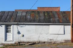 Side view of an old building with patina metal roof and rotting foundation boards Stock Image