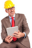 Side view of an old construction engineer with tablet pad Stock Image