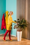Side view of old-fashioned woman. In colorful dress watering plant with watering can at home stock photos
