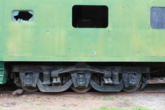 Side view of an old green train passenger car with a broken window, detailing the wheel and undercarriage configuration. Horizontal view Royalty Free Stock Photo