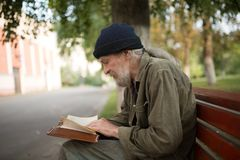 Side view of old homeless man with long grey hair reading a book. Tramp sitting on the bench in the street Royalty Free Stock Image