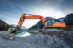 Side view of orange shovel digger on gravel at lake Royalty Free Stock Photo