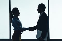Cheerful woman shaking male hand royalty free stock photography