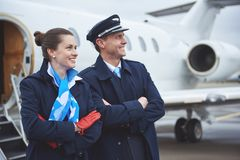 Glad air-hostess and pilot locating near airplane. Side view outgoing young stewardess and beaming aviator looking away while situating near aircraft. Occupation Stock Photo