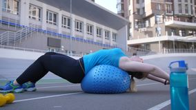 Fat female doing stretching on fitball at stadium. Side view of overweight woman doing stretching exercise lying on fitness ball during sports workout on stadium stock video