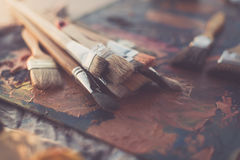 Side view of pallet with oil paint brushstrokes under paintbrush set in an art studio. Stock Images