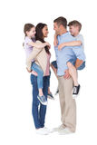 Side view of parents giving piggyback ride to children Stock Images
