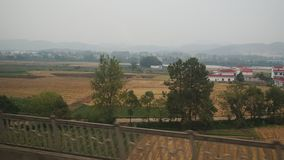 Side view from a passenger train of the countryside of China. Fast motion mode stock video footage