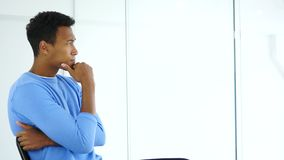 Side view of pensive Afro-American man looking through office window. 4k, high quality stock footage