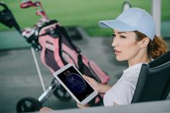 side view of pensive female golf player with tablet in hands