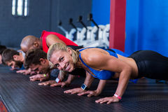 Side view of people doing push-ups in gym Royalty Free Stock Photos