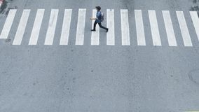 In the side view of people walk fast across the sign of crossroad in the city street. royalty free stock image
