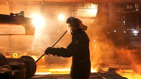 Side view of the perator remove waste from furnace pipe at the iron melting plant. Stock footage. Man worker in heat stock images