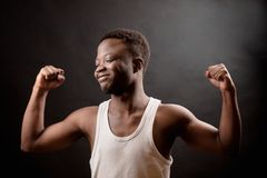 Side view photo of Afro man with closed eyes and smiling showing his biceps Royalty Free Stock Photos