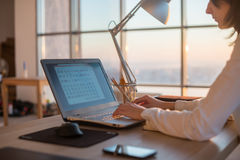 Side view photo of a female programmer using laptop, working, typing, surfing the internet at workplace. stock photography
