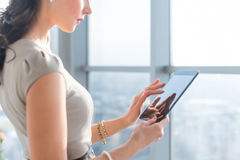 Side view photo of young female teleworker using tablet, searching and browsing information via wi-fi connection Stock Photo