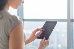 Side view photo of young female teleworker using tablet, searching and browsing information via wi-fi connection. Application in office or at home royalty free stock photos