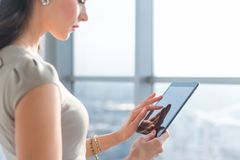 Side view photo of young female teleworker using tablet, searching and browsing information via wi-fi connection. Application in office or at home Stock Images