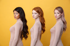 Side view photo of young serious three ladies Stock Images