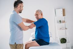 side view of physiotherapist doing massage to senior man stock image