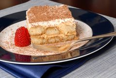 Side view of a piece of tiramisu dusted with cocoa with a fork o royalty free stock image