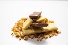 Side view on pile of granola/ muesli spilled among white. brown chocolate bars  on white background. Balanced and healthy royalty free stock image