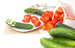Side View of Plated Sliced Tomatoes. An side angled studio view of two sliced field tomatoes and a cucumber with a sprig of dill, basket of ripe field tomatoes Stock Photos
