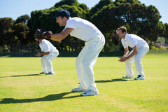Side view of players bending while playing cricket at field. On sunny day stock photo