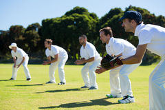Side view of players bending while standing at grassy field. On sunny day royalty free stock image