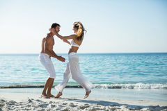 Side view of playful couple at beach Royalty Free Stock Image
