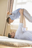 Side view of playful father picking up son while lying on floor at home Stock Photos