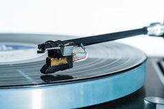 High quality vinyl record deck and tone arm. Side view of a playing vinyl record on vintage hi-fi stereo turntable with tonearm and cartridge in tracks of the LP Royalty Free Stock Photography