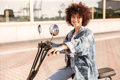 Side view of pleased curly woman sitting on modern motorbike Royalty Free Stock Images