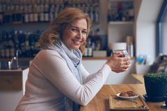 Pleased mature woman smiling at camera during tea break Royalty Free Stock Photo