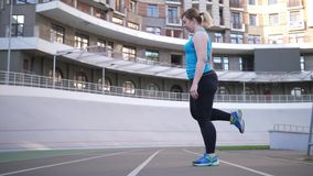 Overweight woman warming up on sports stadium. Side view of plus size female runner stretching leg muscles before workout on city`s sports stadium. Body positive stock video