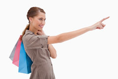 Side view of pointing woman with shopping bags Royalty Free Stock Images