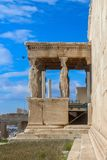 Side view of the Porch of the Caryatids with a bird flying in a very blue sky on the Erechtheion temple dedicated to Athena and Po royalty free stock images
