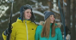 Side view portrait of active young couple enjoying skiing in beautiful winter forest, focus on unrecognizable woman stock footage