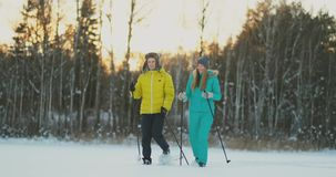 Side view portrait of active young couple enjoying skiing in beautiful winter forest, focus on unrecognizable woman stock video