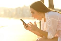 Amazed girl finding smart phone content on the beach at sunset royalty free stock photos