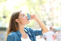 Asthmatic woman using a inhaler outdoors. Side view portrait of an asthmatic woman using a inhaler outdoors in the street Stock Images