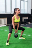 Side view portrait of an athlete woman doing exercises lifting kettlebell in gym working out back, legs muscles. Royalty Free Stock Photos